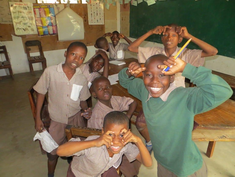 Eight Kenyan school boys in a classroom, smiling.
