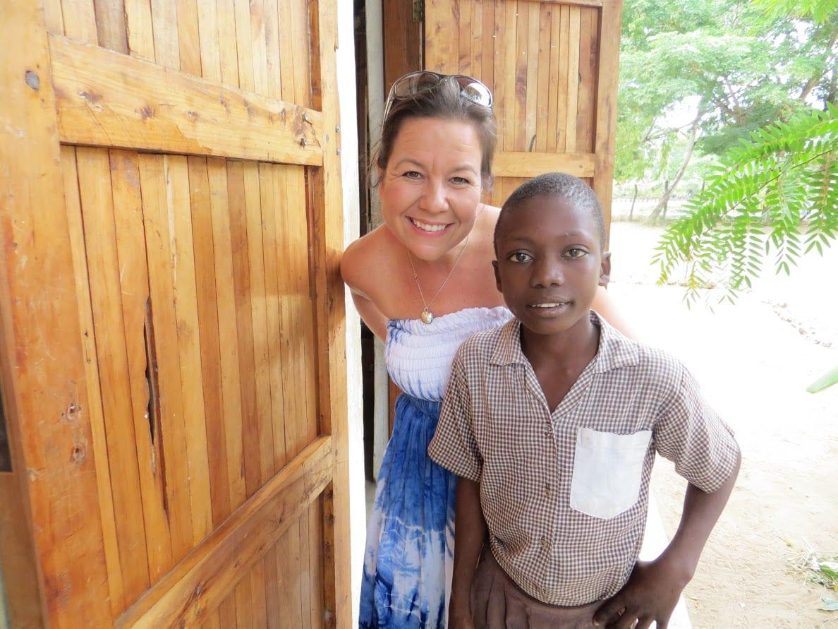 An adult woman standing beside a Kenyan boy outside.