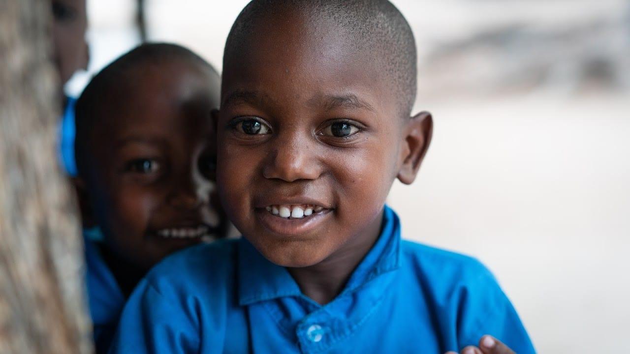 Two Kenyan children smile at school in Gede