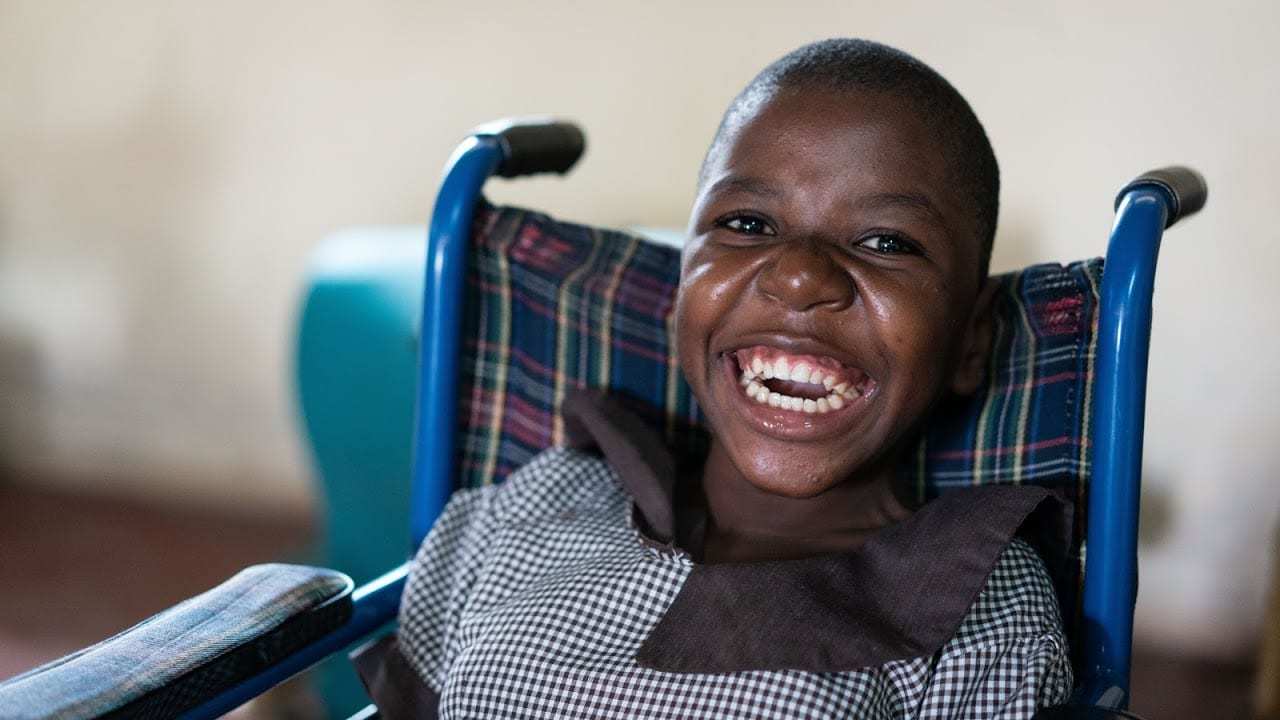 A Kenyan child with a bright smile sitting in a blue wheelchair.