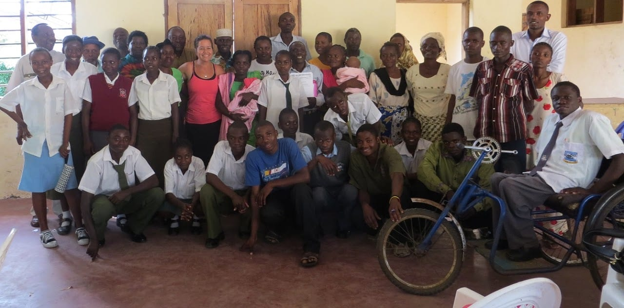 A group of about 40 Kenyans of various ages smiling at the camera.