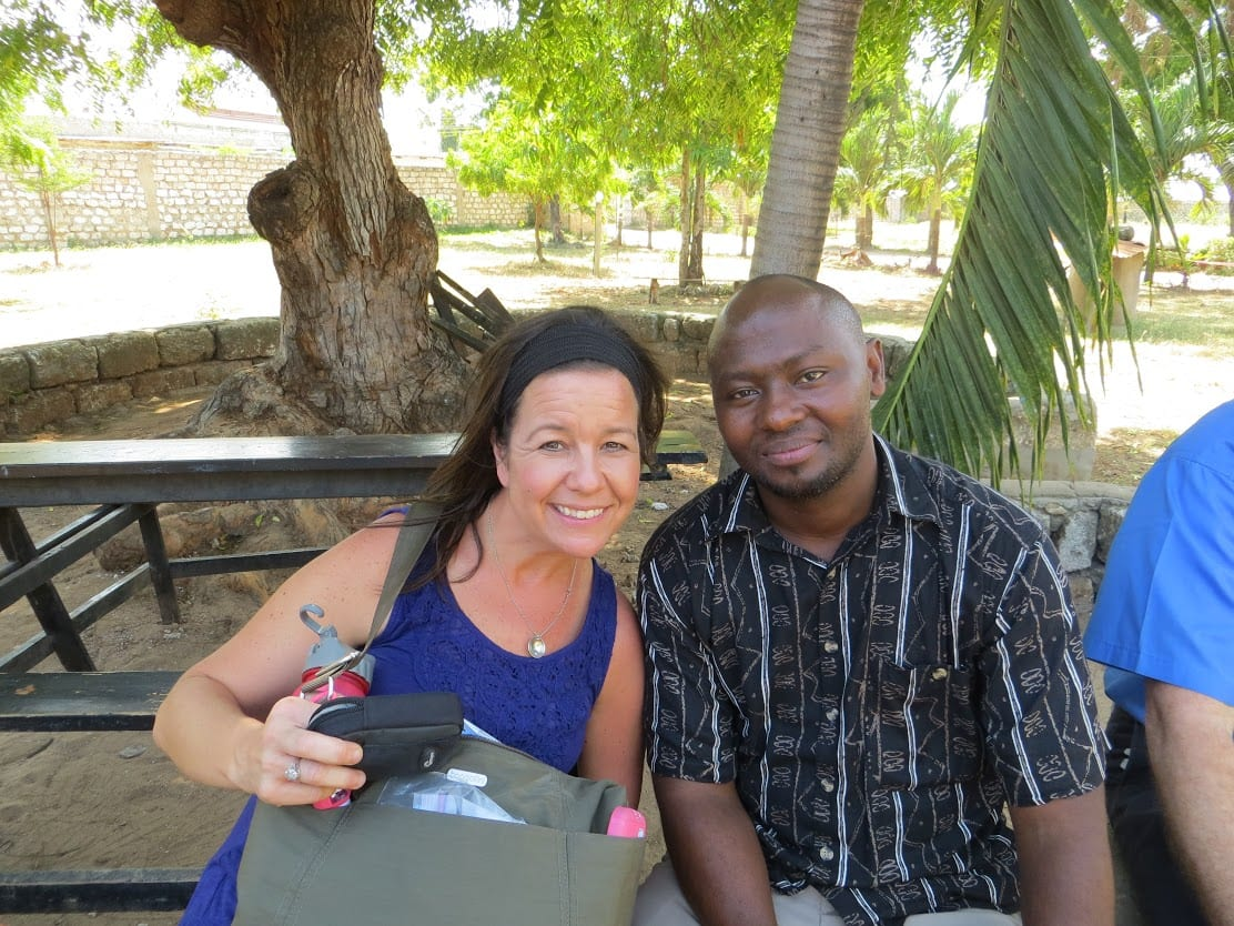 An adult woman and a Kenyan male sitting beneath a tree.