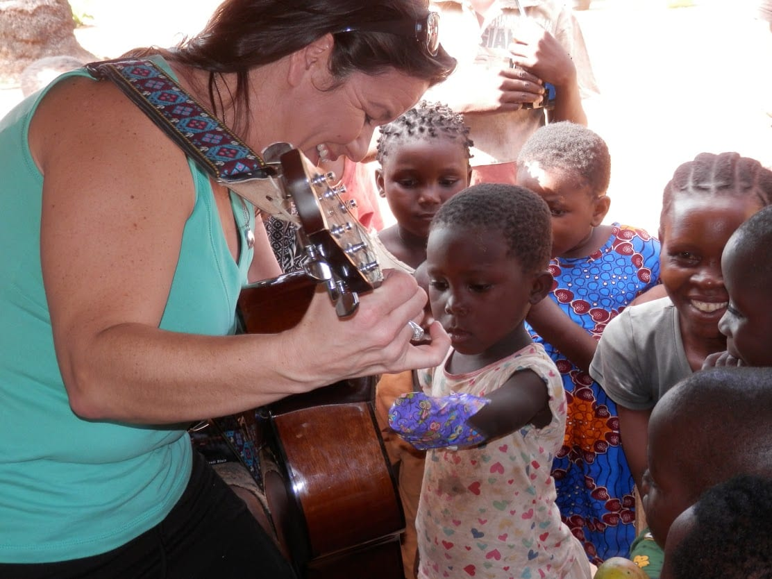 A woman showing a group of young children who to play the guitar.