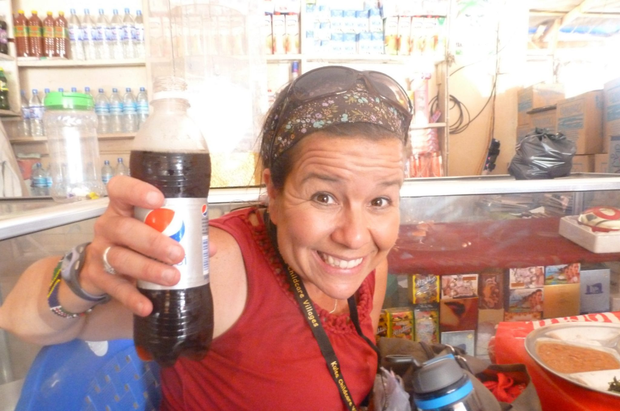 An adult woman smiling, holding a bottle of soda.