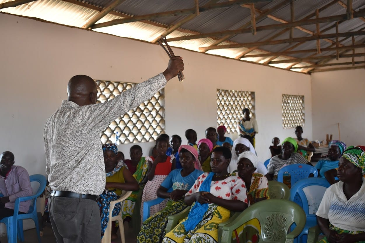 A Kenyan man standing before a group of 20 listeners with one arm raised.