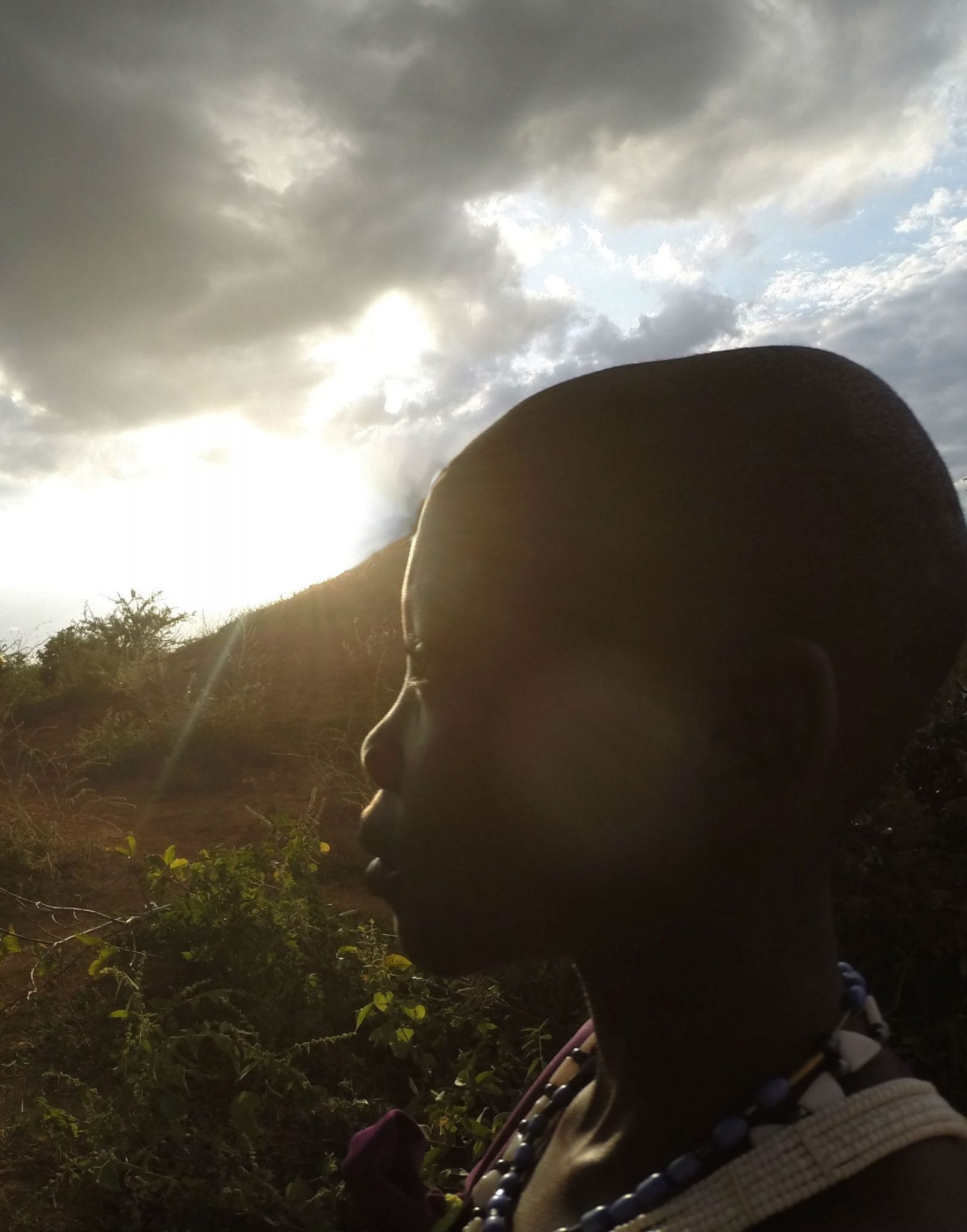 A Kenyan child looking into the distance with the sun shining behind them.