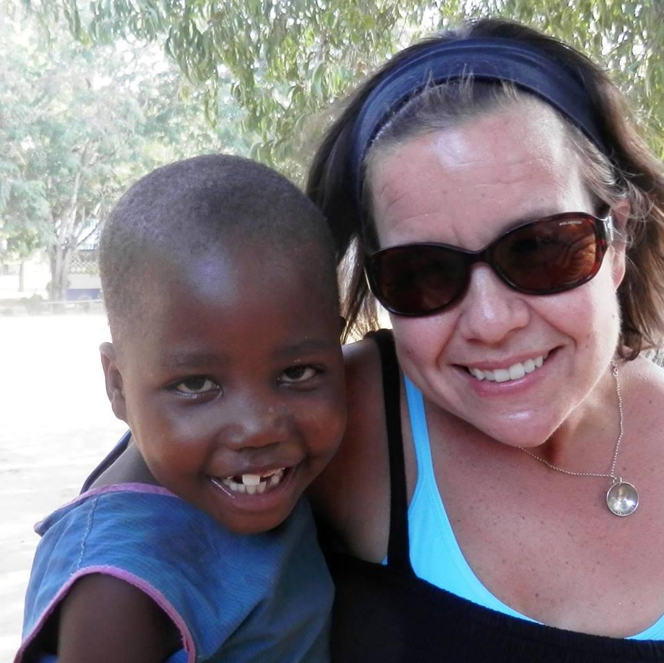 A brunette woman wearing sunglasses holding a smiling Kenyan child.
