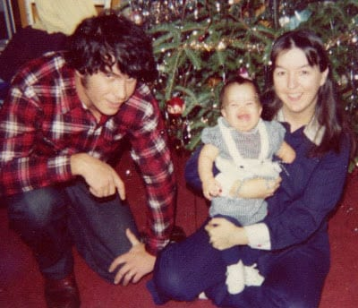 A photo of a a man and a woman holding a baby sitting before a decorated Christmas tree.