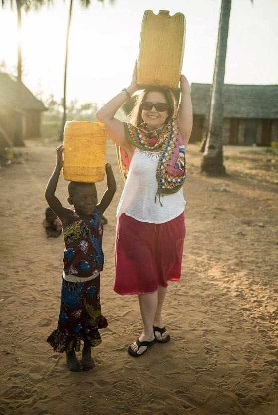 An American woman holding a container above her head standing beside a young child who also has a container