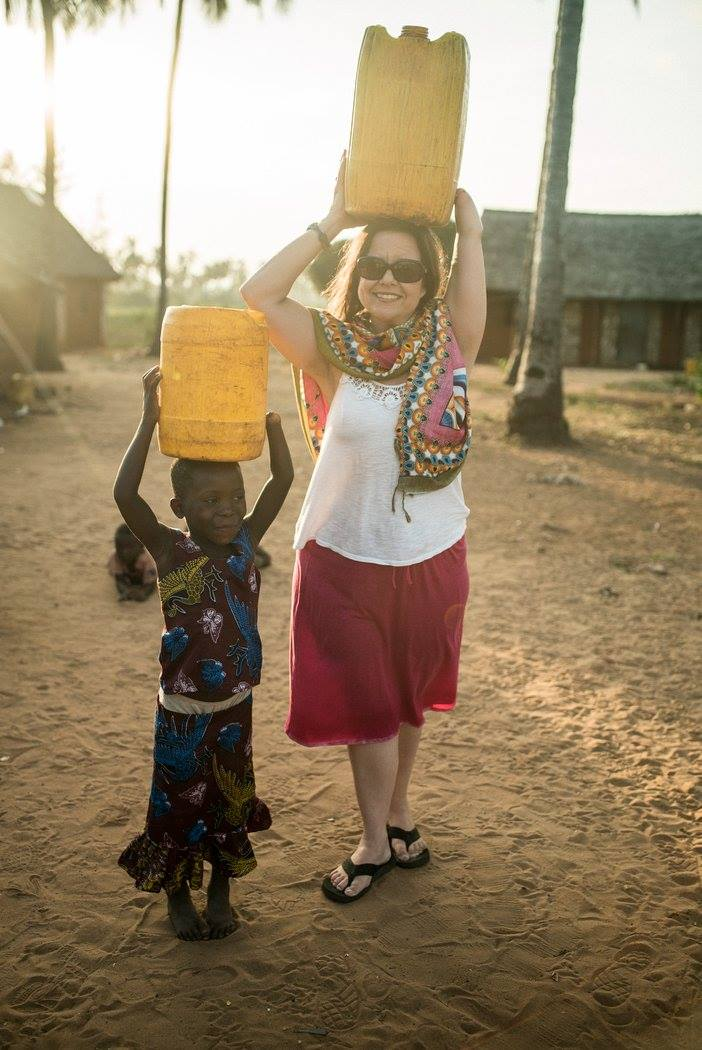 A adult female and a young Kenyan girl holding large containers of water above their heads.