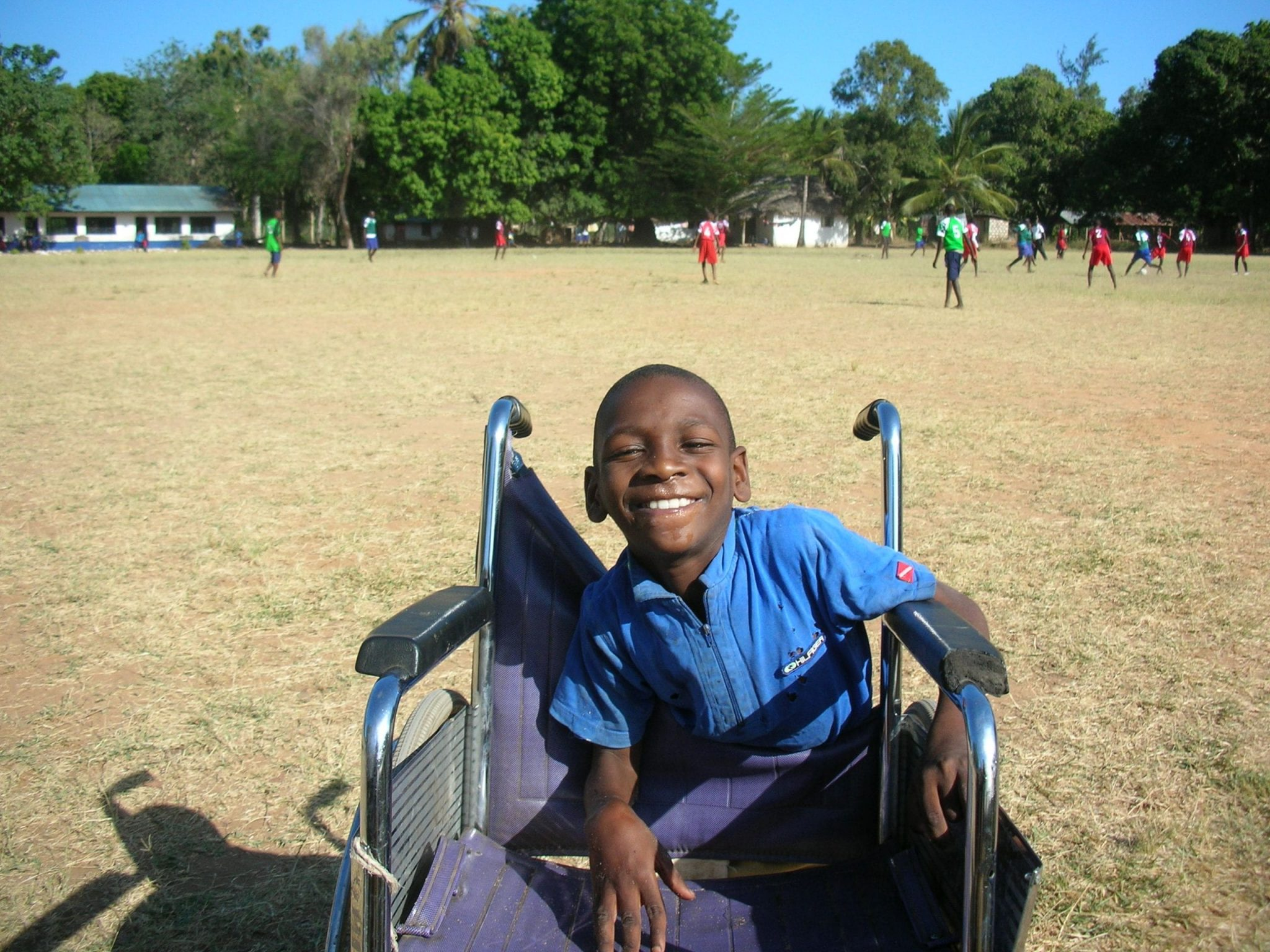 A Kenyan boy smiling and leaning on a wheelchair.