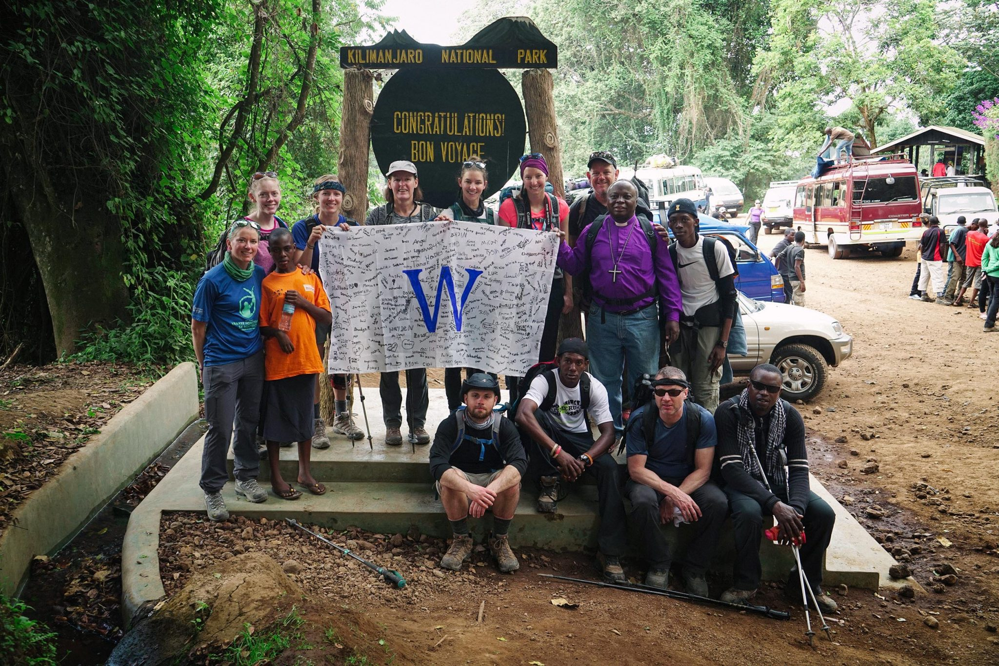 """14 hikers standing together and holding a banner with a large """"W"""" in the center."""