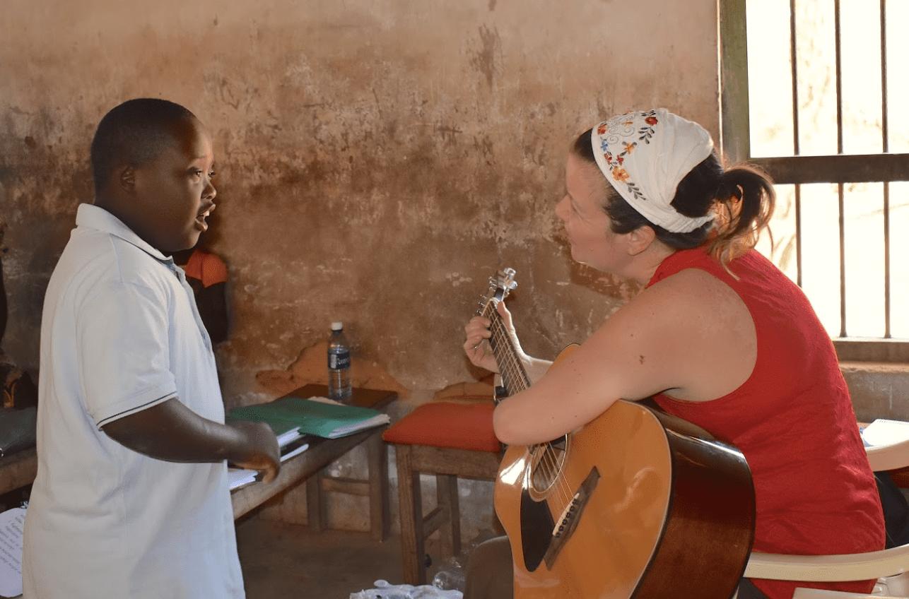 An adult woman playing guitar with a Kenyan boy.