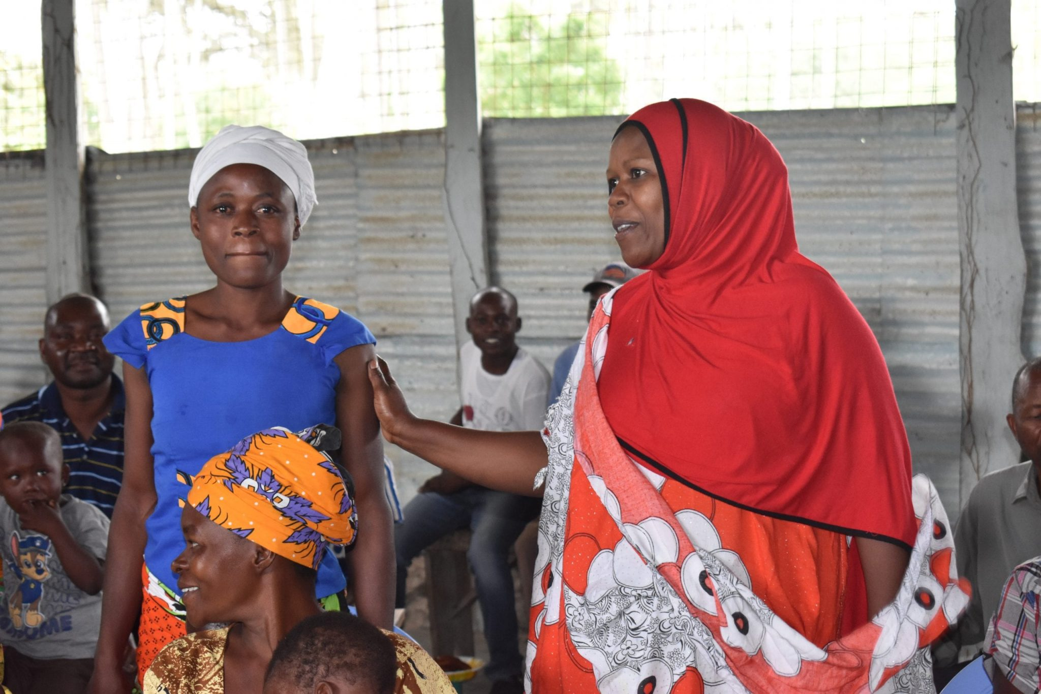 Two Kenyan women standing up with a group of others seated around them.