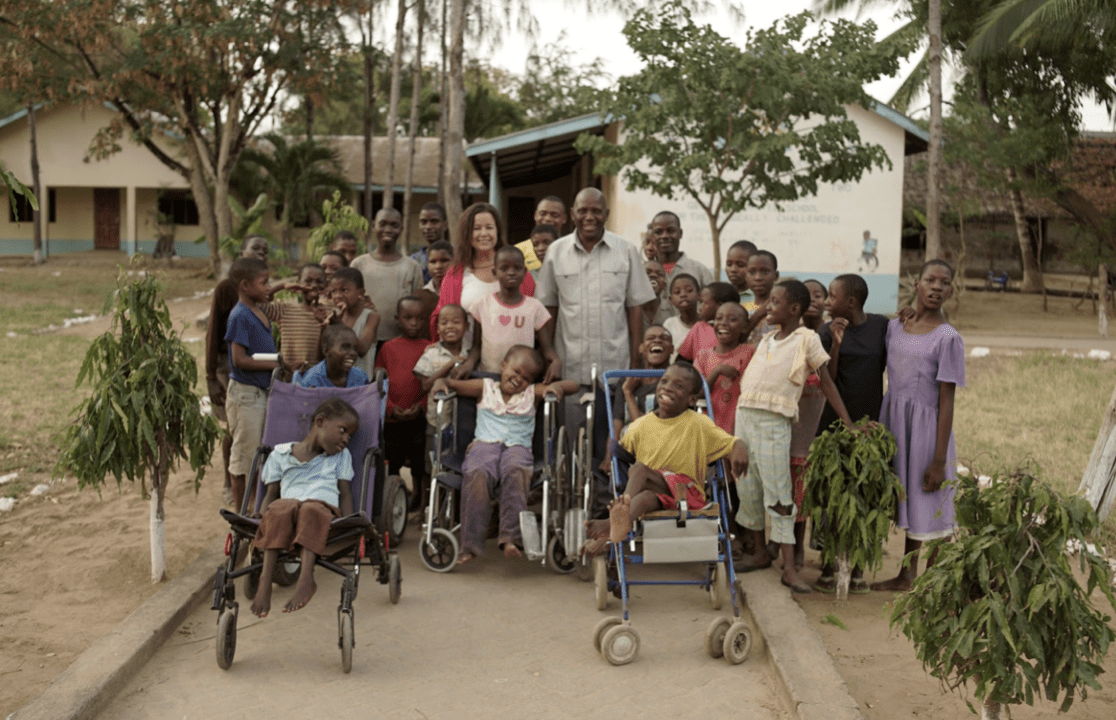 Cindy and Leonard standing with large group of children apart of Kupenda's programs.