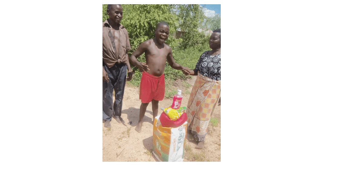 Child smiling with two adults after receiving Kupenda food relief.