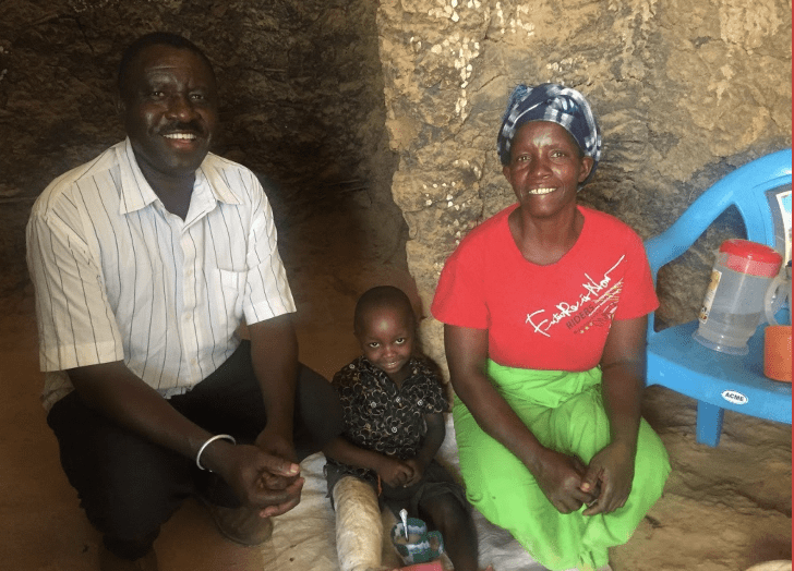 Kenyan parents with small child smiling and sitting together.
