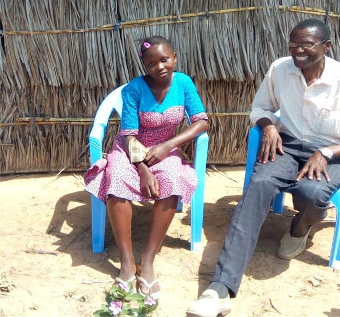 Kenyan pastor sitting beside a young girl in blue chairs outside