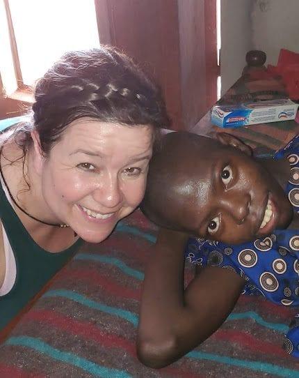 An adult woman smiling beside a Kenyan young woman.