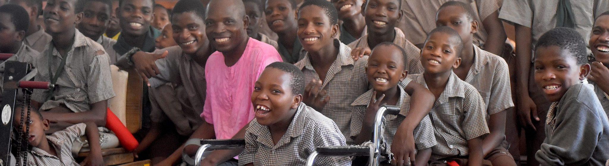 20 Kenyan boys sitting together and smiling.