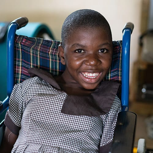 A young girl sitting in a blue wheelchair and smiling.