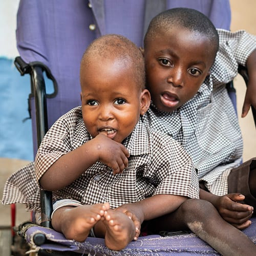 2 young Kenyan boys seated in a wheelchair.
