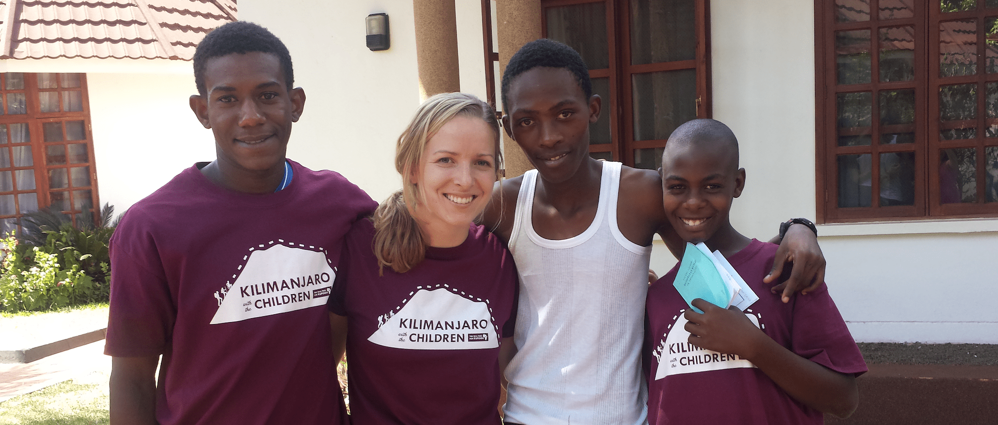 Three Kenyan children standing with a female smiling.