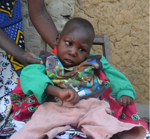 A young Kenyan child seated on a wooden chair, receiving help to stay sitting up.