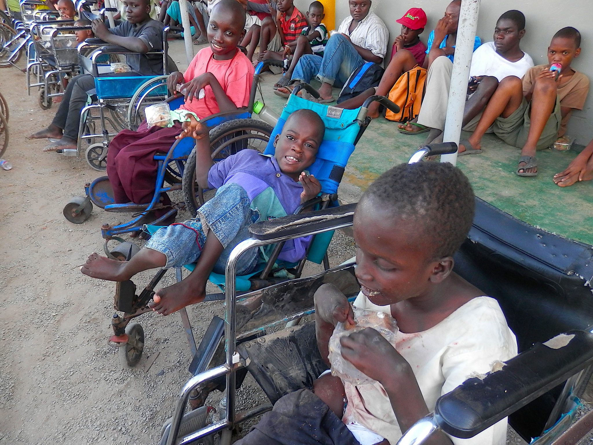 Two long rows of Kenyan boys. Three young boys in wheelchair are most prominent in the photo.