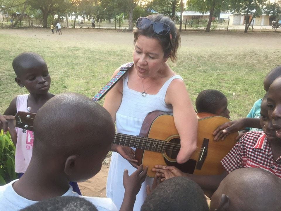 A woman playing guitar for a group of interested young boys