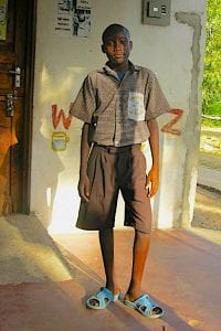 Kenyan teen, Amani Patrick, standing outside of a building