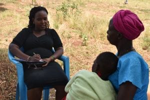 Kenyan woman talks to a mother and her child outside