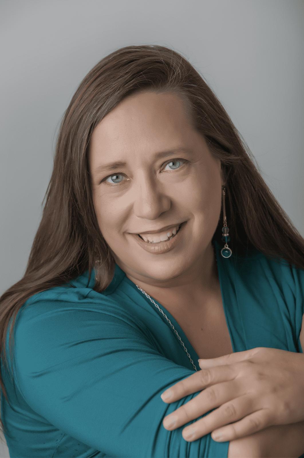 Headshot of a woman, Michele Reber, wearing a blue shirt