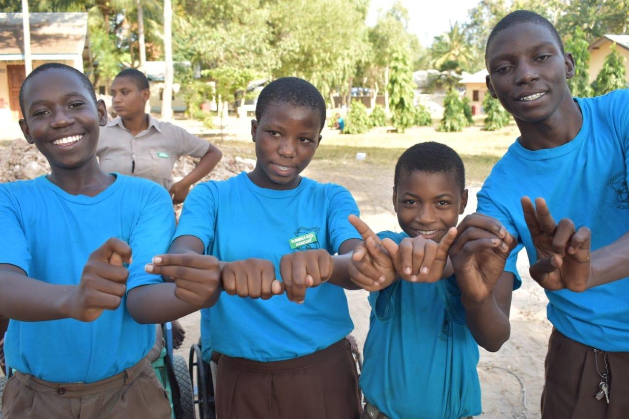 Four Kenyan boys in matching blue shirts smile at the camera.