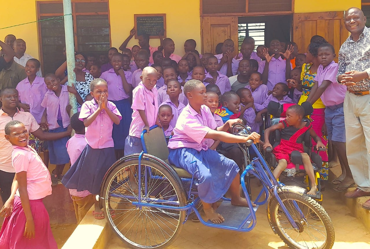 A large group of Kenyan children in purple shirts, featuring a young boy riding a blue bicycle in front of the group.