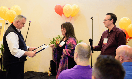 A man handing an award to a woman, there are three individuals who can be seen in the audience.