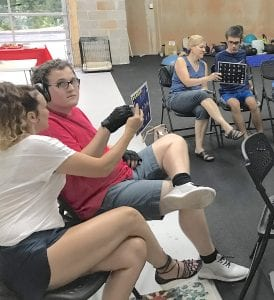 Two men and two women sitting in folding chairs