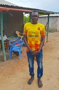Kenyan boy in a vibrant yellow shirt standing outside
