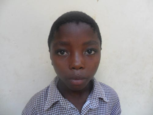 Young boy wearing a blue shirt looking at the camera